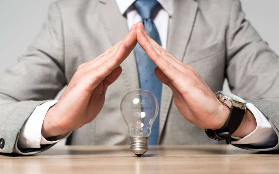 cropped view of businessman showing protection gesture above light bulb isolated on grey