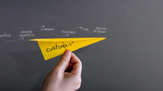 customer value journey concept Customer Journey and Experience Concept. Hand Raise Up a Paper Plane against the Wall, Graphic and Text about Client's Journey as background. Side View